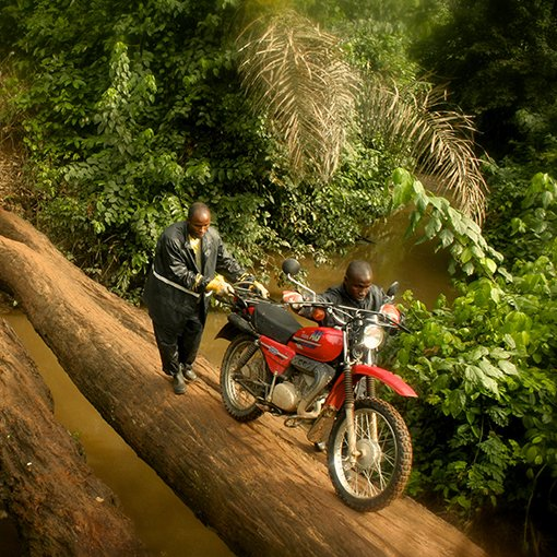 Men pushing motorbike over log